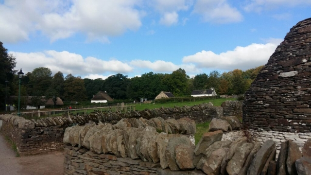 Outdoor view of the St Fagans museum including historic buildings, green gardens and stone fences