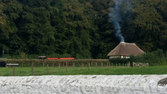 Outdoor view including a historic building with smoke coming out of its chimney