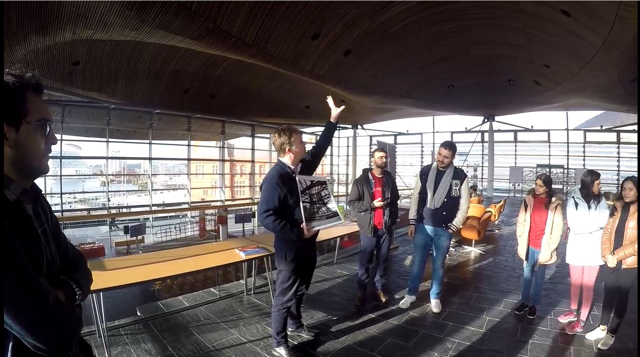 Students in Senedd building listening to Senedd staff giving information about the roof structure