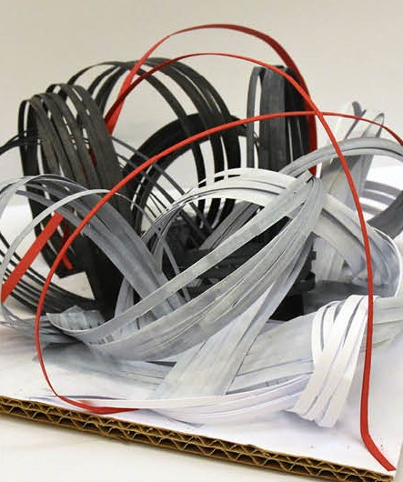 Swirls of red, black, grey and white paper strips representing sound.